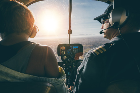 man flying: Rear view of male and female pilots flying a helicopter on sunny day. Man flying a helicopter with his copilot looking outside the aircraft.