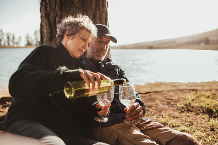 Senior man and woman enjoying outdoors camping on picnic area near Lake. Woman pouring wine in glasses, both sitting under a tree at campsite. Stock Photo