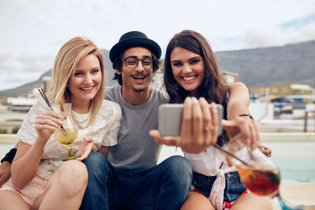Group of friends taking selfie on a smart phone. Young man and women with drinks taking a self portrait on cell phone. Young people on rooftop party, capturing the moment on camera.