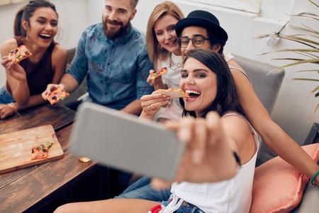 Grupo de jovens multirraciais que tomam um selfie ao comer pizza. Mulher nova que come a pizza seus amigos sentados ao redor durante uma festa.