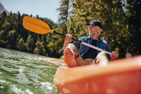 outdoor exercise: Portrait of a mature man with kayak in a lake. Caucasian man paddling a kayak on summer day.