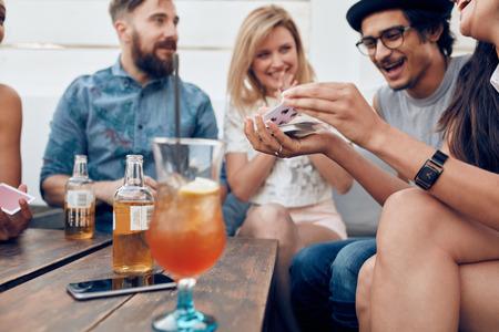 Groep jonge mensen zitten aan een houten tafel en speelkaarten. Vrouw schuifelen kaarten tijdens de vergadering met haar vrienden in de partij. Stockfoto