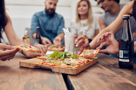 comiendo: Cierre de tiro de pizza en la mesa, con el grupo de jóvenes sentados alrededor y recogiendo una porción. Amigos de fiesta y comer pizza.