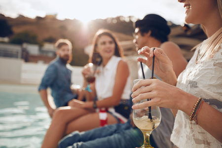 poolside: Woman holding a cocktail glass while sitting on the edge of swimming pool with friends. Young people enjoying a poolside party with drinks. Focus on hand and cocktail glass.
