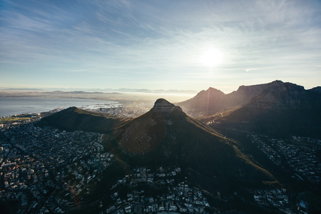 birds eye: Aerial view of Cape Town city with Table Mountain,  Lions Head and Devils Peak. Birds eye view of city of cape town under blue sky and bright sunlight. Stock Photo