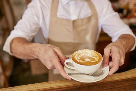 Primer plano de hombre en la plataforma que sirve café mientras está de pie en la cafetería. Barista que le da una taza de café recién hecho en el café.