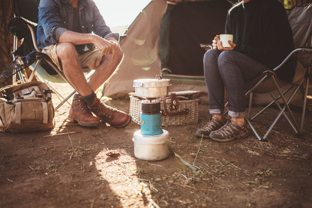 Cropped shot of mature couple sitting around a camp stove. Man and woman sitting in chair outside tent at their campsite.