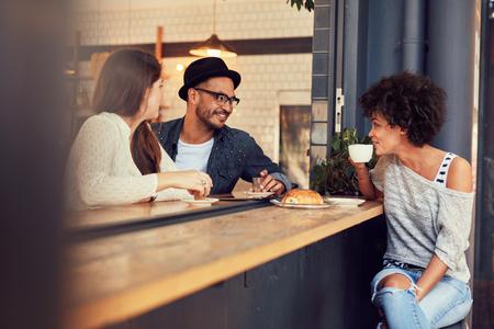 Счастливые молодые люди, сидящие в кафе и разговаривают друг с другом. Группа молодых друзей и сообщающихся с удовольствием в кафе.