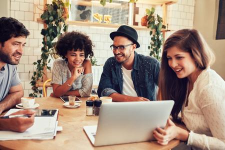 Skupina přátel visí v kavárně s notebookem mezi nimi. Šťastné mladých lidí sedí v restauraci pomocí přenosného počítače. Reklamní fotografie