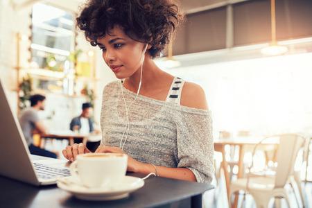 カフェでノート パソコンを使用してイヤホンで魅力的な若い女性の肖像画。コーヒー ショップでノート パソコンに働くアフリカ系アメリカ人女性。