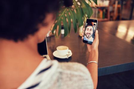 一個年輕女子和通過智能手機進行視頻通話互相交談。年輕女子有手機與男子視頻聊天。女子坐在在咖啡店。