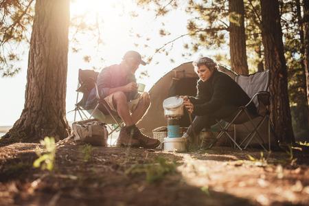 Senior Paar Kochen und Speisen im Freien auf einem Camping-Ausflug. Ältere Mann und Frau vor dem Zelt auf dem Campingplatz an einem Sommertag sitzt.