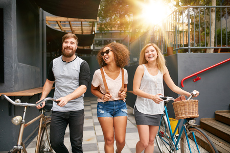 anden: Tres adultos jóvenes caminando juntos se divierten. Los jóvenes con bicicletas caminando al aire libre en la ciudad.