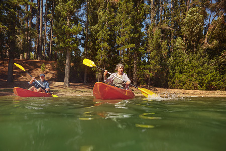 Portrait of a mature couple canoeing on a lake during a camping trip. Active senior couple in two single kayaks in the lake. Banco de Imagens