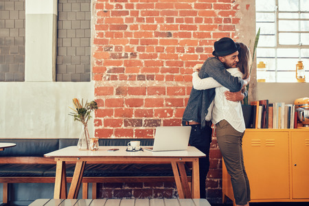 personas abrazadas: Retrato de hombre y mujer abrazos y saludo entre sí en una cafetería, Reunión de los pares en un café.