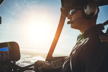 Close up of a pilot flying a helicopter with sun flare entering the cockpit.