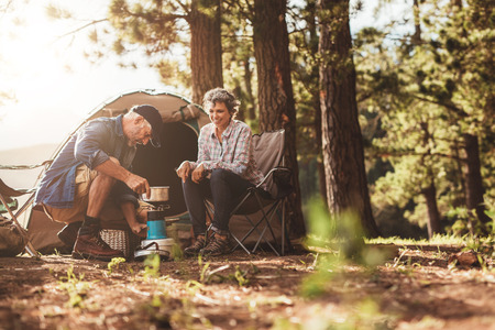 Happy campers outdoors in the wilderness and making coffee on a stove. Senior couple on a camping holiday. Archivio Fotografico