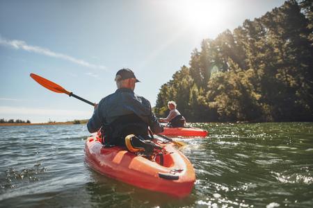 バック グラウンドで女性と湖でカヌー中年の男性の屋外撮影。晴れた日に湖でカヤックのカップル。