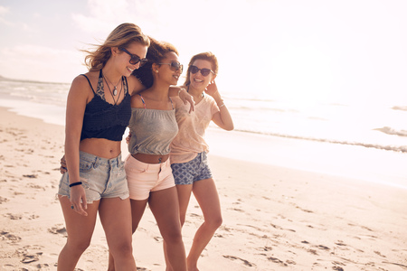 young friends: Portrait of three young female friends walking on the sea shore. Multiracial young women strolling along a beach on a summer day.