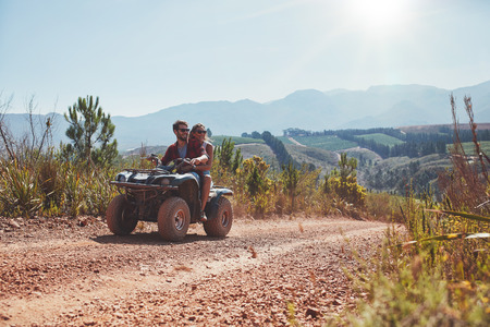 Young man and woman driving a quad bike on country road on a summer day. Couple on holiday enjoying on a ATV bike ride.