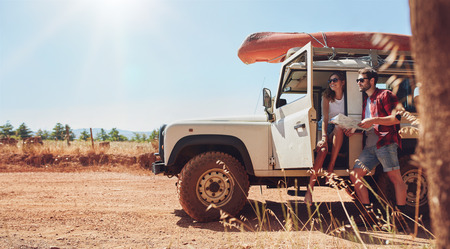 Młoda para z samochodu na podróż mapie odczytu dla kierunków. Młody mężczyzna i kobieta biorąc przerwę od podróży.