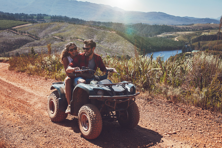 quad: Young couple having fun on mountain while driving a quad bike on a summer day. Young man and woman on an ATV.