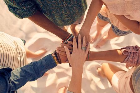 Gruppe von jungen Männern und Frauen, die Einheit zeigen. Gruppe von jungen Freunden ihre Hände zusammen am Strand setzen. Lizenzfreie Bilder