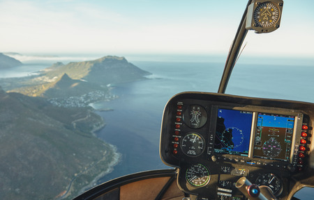 Aerial view from a helicopter cockpit flying over Cape town. Interior of helicopter cockpit with instruments panel. Stock Photo