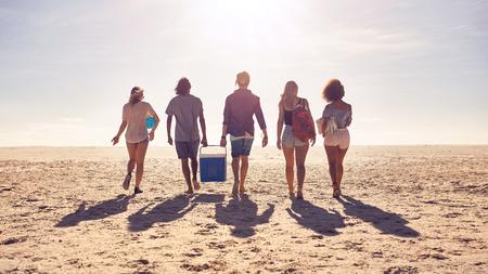 朋友走在沙灘上,並互相幫助,同時搭載了保溫箱組的後視圖肖像。年輕人在一個夏季的一天海邊。 版權商用圖片