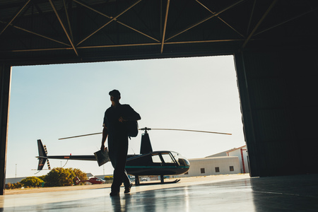 parked: Silhouette of a pilot arriving at the airport with a helicopter in background. Helicopter pilot in airplane hangar.