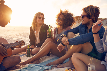 Portrait of group of young friends having a party on the beach in evening. Men and women drinking beers and listening to friend playing guitar. Stock Photo