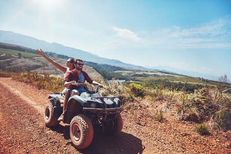 girlfriend: Young couple on an off road adventure. Man driving quad bike with girlfriend sitting behind and enjoying the ride in nature. Stock Photo