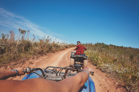 quad: Young man on quad bike. Young man driving all terrain vehicle in nature. View from a ATV.