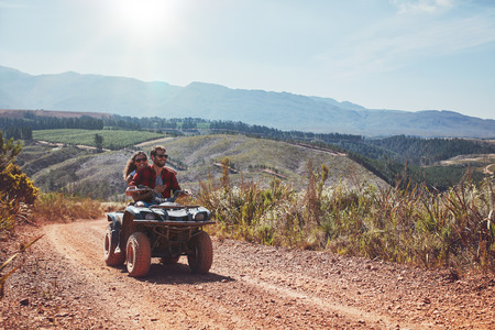 off road vehicle: Young man and woman having fun while driving a quad bike. Young couple enjoying off road vehicle ride on a summer day.
