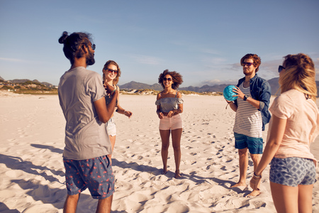weekend activities: Group of young people standing in circle on the beach and playing with ball. Young friends playing ball game on a sandy beach.