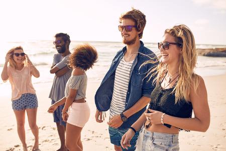 Grupo de amigos que andam ao longo de uma praia no verão. Jovens felizes que apreciam um dia na praia.