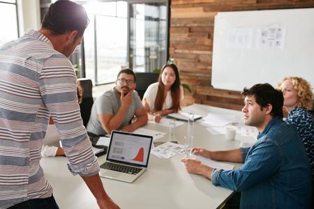 cooperacion: Hombre joven que da la presentación de negocios en la computadora portátil a los colegas que se sientan alrededor de la mesa en la sala de conferencias.