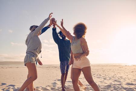 快樂的朋友組擊掌高在沙灘上,在夏季的樂趣。混血人慶祝成功。