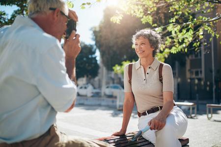 Donna attraente senior che propone per un'immagine. Anziano, scattare, foto, moglie, seduta, panca, città.