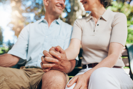 cropped shot: Cropped shot of mature couple holding hands while sitting together on a park bench. Focus on hands. Stock Photo