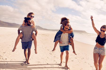 piggyback ride: Diverse group of young friends having fun on the beach , with men giving piggyback ride to women. Happy young people enjoying summer vacation on the beach. Stock Photo