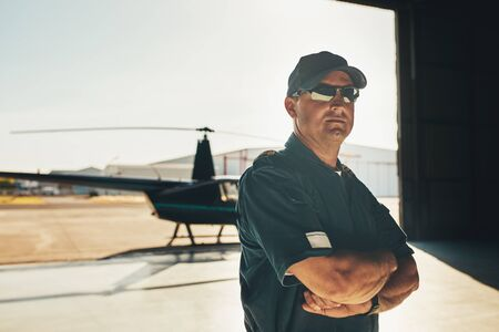air plane: Portrait of confident pilot in uniform standing with his arms crossed in airplane hangar with a helicopter in background