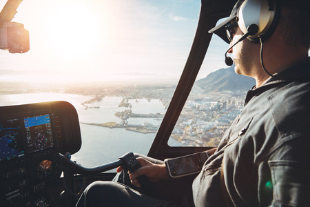 Male pilot in cockpit of a helicopter flying over cape town city on a bright sunny day.