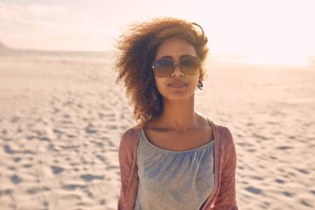 一个迷人的年轻女子站在沙滩上的肖像。她戴着太阳镜看着照相机。