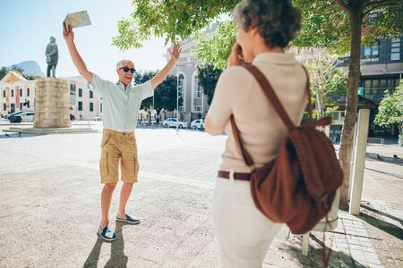 family vacation: Woman taking photos of an excited senior man in the city. Mature couple enjoying themselves on a vacation. Stock Photo