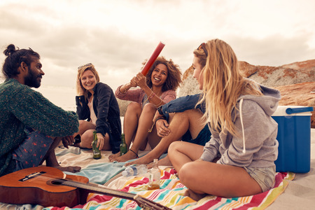 Portrait of happy young people having fun at beach party. Group of friends having a beach party together and celebrating with confetti.
