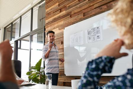 reunion de trabajo: El hombre joven que discute el nuevo diseño de aplicaciones móviles a bordo de blanco con colegas durante una reunión. Presentación del asunto en la sala de juntas.