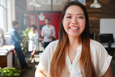 Portrait of cheerful young asian woman standing in office with coworkers talking in background. Female creative professional looking at camera and smiling. Stock Photo