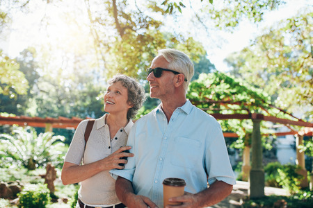 admiring: Portrait of senior couple together in a park looking at a view. Mature caucasian couple admiring a view. Stock Photo