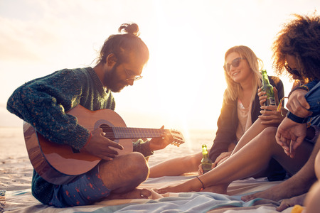 Young man playing guitar for friends sitting on the beach. Group of friends partying and listening to music at sunset.